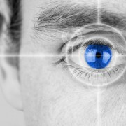 27554617 - vision concept with a greyscale image of a mans eye with a crosshair focused on his iris which has been selectively colored blue.