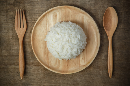 42742518 - top view of thai jasmine rice in wooden dish with napery and wooden spoon - soft focus