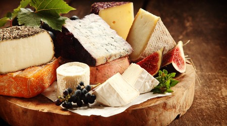 49118097 - delicious gourmet cheese platter with a wide assortment of soft and semi-hard cheeses served with sliced sweet fresh figs and grapes on a rustic wooden table with background shadow